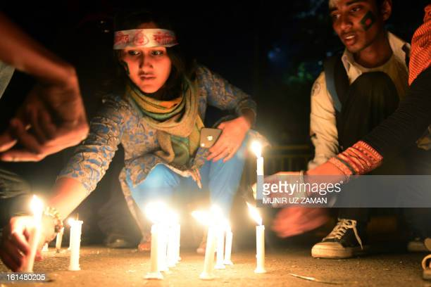 Bangladeshi social activists light candels in Dhaka on February 11 as they take part in seven day of protest calling for quick executions of the 10...
