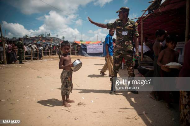 A Bangladeshi soldier gestures as a Rohingya Muslim refugee child waits to receive his daily meal at a food distribution in Balukhali refugee camp...