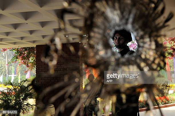A Bangladeshi soldier is seen through a bulletshattered glass door of the officers mess at the Bangladesh Rifles headquarters in Dhaka on March 3...