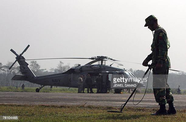 A Bangladeshi soldier scans the outfield of the Barishal airportturnedmilitary base as a US Navy helicopter sits idle in Barishal 27 November 2007 US...