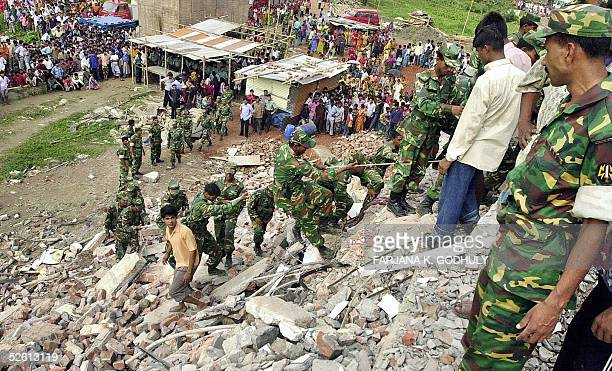 Bangladeshi soldiers climb the debris of a collapsed factory looking for survivors while villagers and relatives gather nearby for news in Palash...