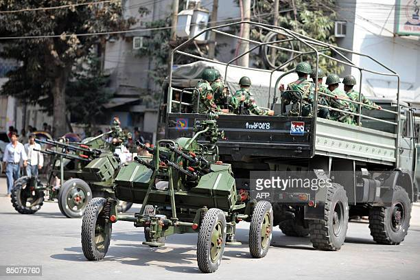 Bangladeshi soldiers sit in a truck with a machine gun turret in tow as they gather outside the Bangladesh Rifles headquarters complex in Dhaka on...