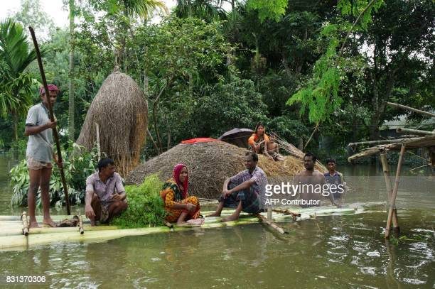 Bangladeshi stand on a raft made of banana tree trunks in an area submerged by flood in Kurigram northern Bangladesh on August 14 2017 Major rivers...