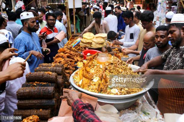 Bangladeshi street vendors sell iftar foods for breaking the daytime fast on the first day of holy month of Ramadan at a traditional iftar market in...
