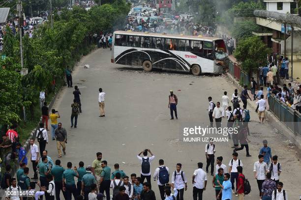 Bangladeshi students and police stand near a bus set alight during a student protest in Dhaka on July 31 following the deaths on July 30 of two...