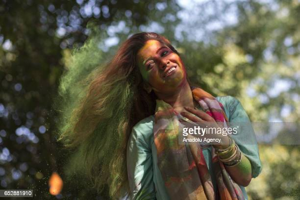 Bangladeshi student's face is covered with colored powder during Holi celebrations at the Fine Arts Institute of Dhaka University in Dhaka Bangladesh...