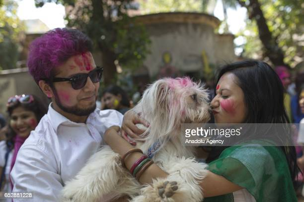 Bangladeshi students hold a dog as they play with colored powder during Holi celebrations at the Fine Arts Institute of Dhaka University in Dhaka...
