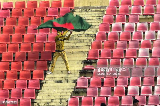 A Bangladeshi supporter dressed as a tiger weaves Bangladesh's national flag during the fifth and final day of the first cricket Test between...