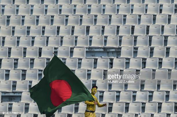 Bangladeshi supporter dressed as a tiger weaves Bangladesh's national flag during the fifth and final day of the first cricket Test between...