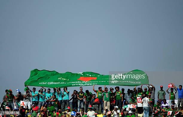Bangladeshi supporters hold Bangladesh's national flag during the Cricket World Cup tournament match between Bangladesh and The Netherlands at Zahur...