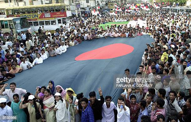 Bangladeshi supporters of the opposition Awami League party carry a huge national flag and party flags as AL leader Sheikh Hasina Wajed leads an...