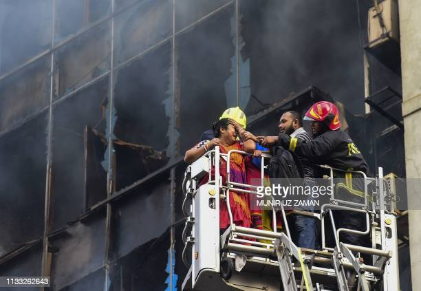 A Bangladeshi survivor reacts after being rescued by firefighters from a burning office building in Dhaka on March 28 2019 A huge fire tore through a...