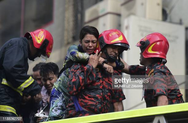 Bangladeshi survivor reacts after being rescued by firefighters from a burning office building in Dhaka on March 28 2019 A huge fire tore through a...