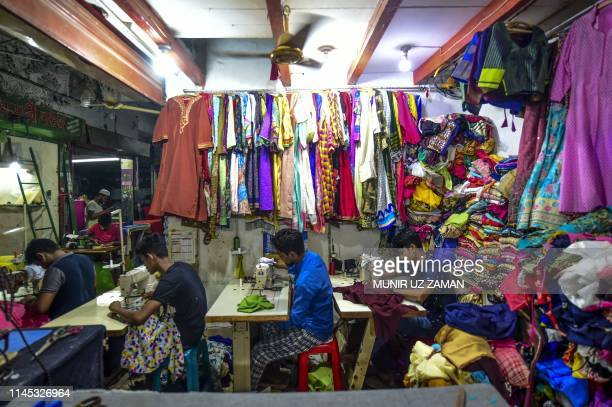 Bangladeshi tailors work ahead of EidalFitr in Dhaka on May 21 2019 The Dhaka New Market built between 1952 and 1954 is a shopping area catering...