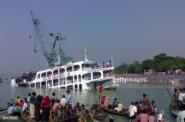 Bangladeshi villagers gather at the riverside as the capsized ferry MV Coco4 is hoisted by the salvage vessel MV Hamza in village Bhola some 255 kms...