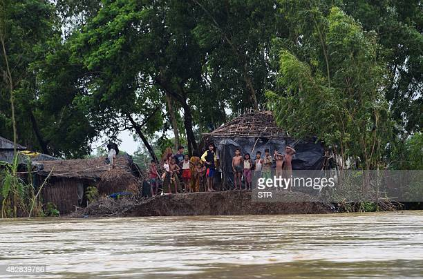 Bangladeshi villagers stand near a broken embankment in Cox's Bazar on August 2 2015 The area was hit by heavy rains brought to the area by Cyclone...