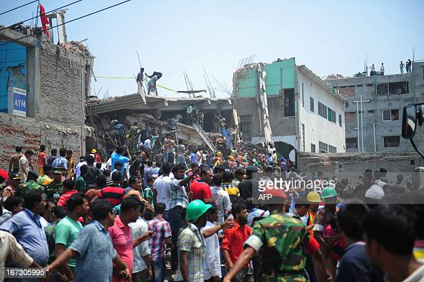 Bangladeshi volunteers and rescue workers are picture at the scene after an eightstorey building collapsed in Savar on the outskirts of Dhaka on...