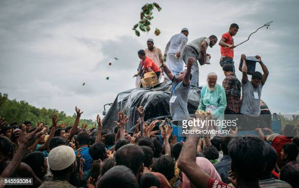 TOPSHOT Bangladeshi volunteers from the Chhagalnaiya village council distribute food donations to Rohingya Muslim refugees at Naikhongchhari in...