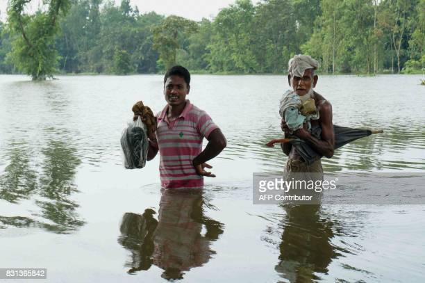 TOPSHOT Bangladeshi walk in water in an area submerged by flood in Kurigram northern Bangladesh on August 14 2017 At least 175 people have died and...