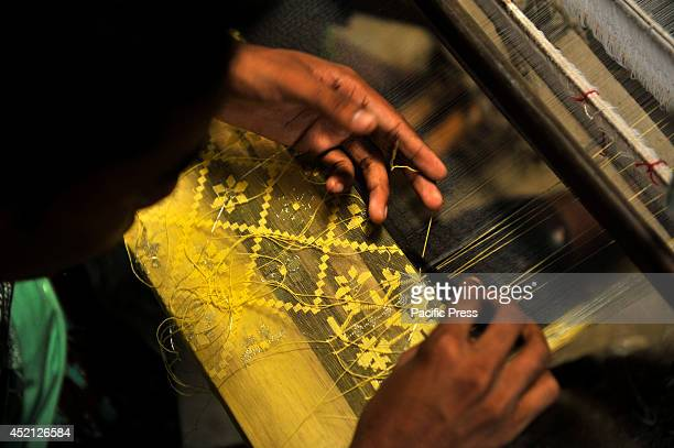 Bangladeshi weaver puts pattern designs in a Jamdani sari. Jamdani is the finest Muslin textile produced in Dhaka District. It is a time consuming...