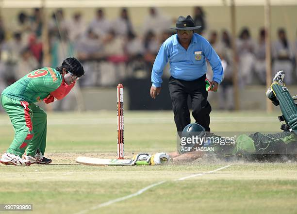 Bangladeshi wicket keeper Nigar Sultana attempts a run out as Pakistani cricketer Bismah Mahroof makes her ground during the second T20 match between...