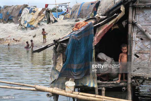 A Bangladeshi woman goes about her daily tasks in a basic hut along the river's edge in Dhaka 07 September 2007 Bangladesh is braced for potentially...