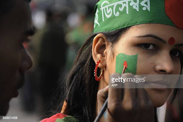 A Bangladeshi woman has the national flag painted on her cheek during a rally held to mark the country's 38th Victory Day in Dhaka on December 16...