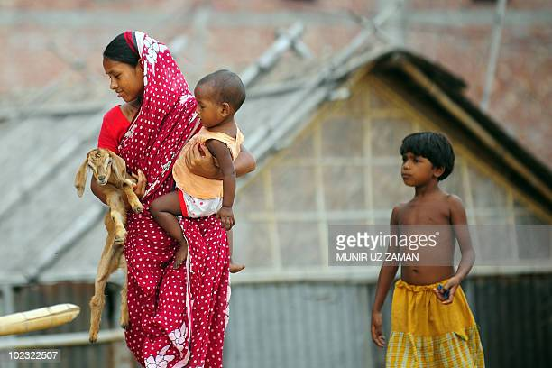 A Bangladeshi woman holds a goat and a child in Dhaka on June 192010 By some estimates between 35 and 77 million people have been chronically exposed...