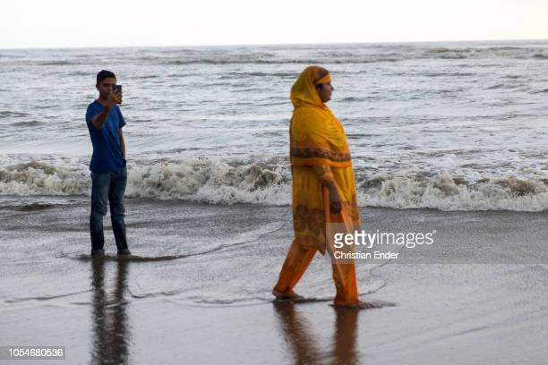 Cox´s Bazar Bangladesh October 14 2018 A Bangladeshi woman in traditional dress enjoys the evening sun on the beach while a man takes a selfie with...