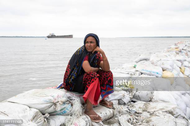 Bangladeshi woman Rubi Begum sits on sandbag embankment that was breached by high water in Khulna Bani Shanta on May 4 as Cyclone Fani reached...