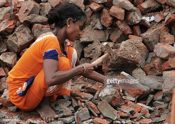 A Bangladeshi woman squats as she breaks bricks in the Gaptoli brick breaking yard in Dhaka 07 September 2007 With over half of the population living...