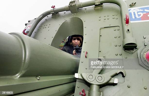 Bangladeshi woman takes a closer look to an army tank during a military public show at the National parade Square in Dhaka 17 December 2003 The show...