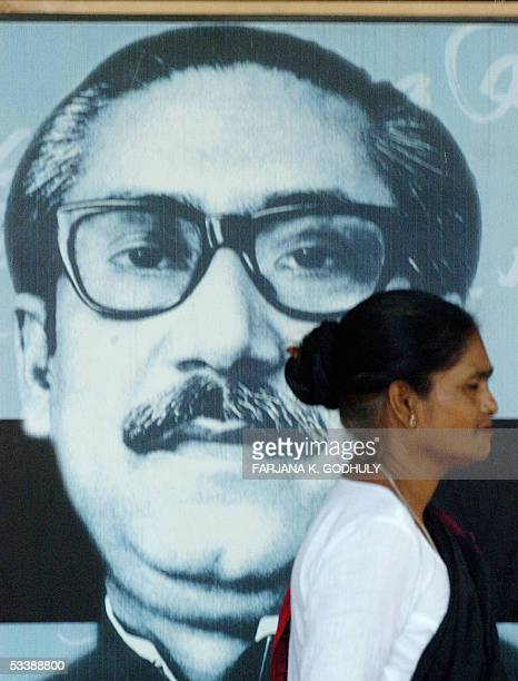 Bangladeshi woman walks past a portrait of Bangladesh's founder Sheikh Mujibur Rahman during a general strike called by the main opposition party...