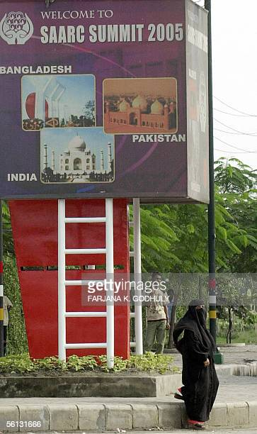 Bangladeshi woman wearing a burqa walks past a sign for the13th South Asian Association for Regional Cooperations summit in Dhaka 10 November 2005...