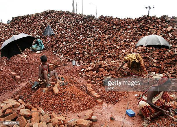 Bangladeshi women and a young boy break bricks in the Gaptoli brick breaking yard in Dhaka 07 September 2007 With over half of the population living...