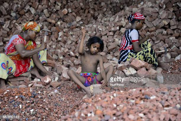 Bangladeshi women and Childs break bricks at Demra brick breaking yard in Dhaka Bangladesh On May 13 2017 With over half of the population living...