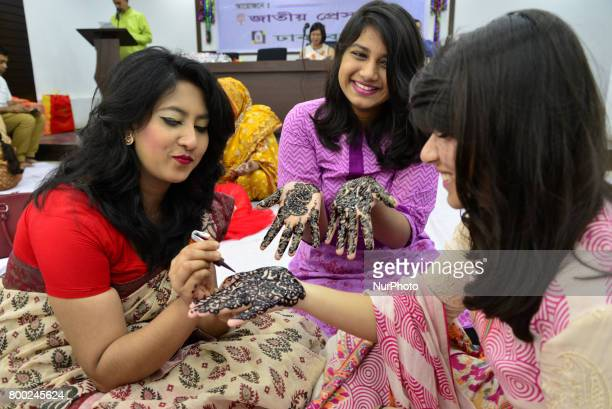 Bangladeshi women decorate hands with henna during a henna design festival organized by Dhaka Bashi organization ahead of the EidulFitr festival in...