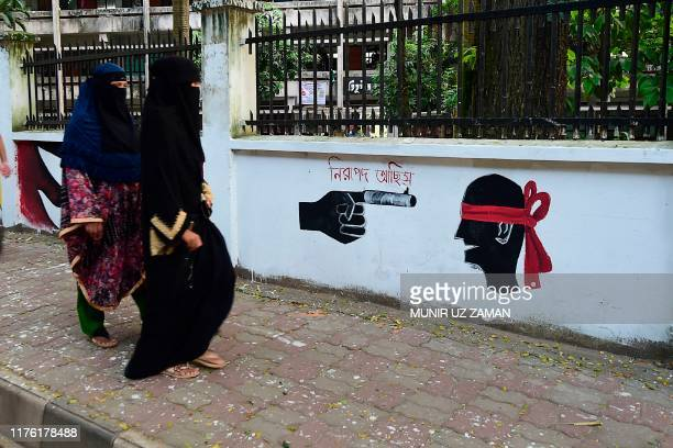 Bangladeshi women walk past a wall painting made by students of Bangladesh University of Engineering and Technology in the BUET campus in Dhaka on...