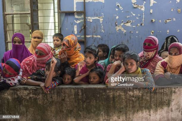 Bangladeshi women watch the arrival of dead bodies of Rohingya Muslim refugees at a school near Inani beach in Cox's Bazar district on September 29...