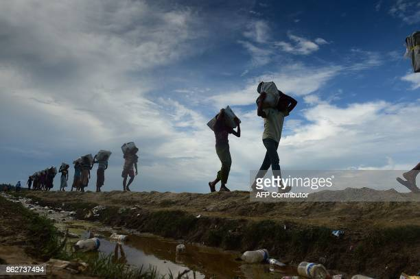 Bangladeshi workers carry relief materials for Rohingya refugees stranded in the no man's land area between Bangladesh and Myanmar in the Palongkhali...