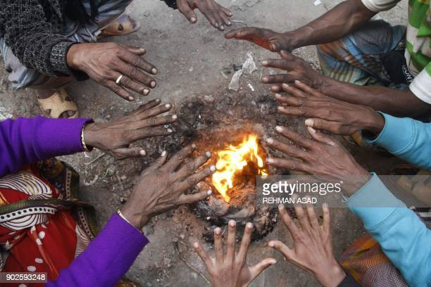 Bangladeshi workers warm themselves around a bonfire in Dhaka on January 8 2018 Bangladesh recorded its lowest ever temperature in history at 26...