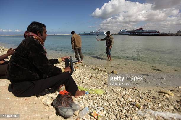 Bangladeshi workers wash their socks with sea water at a makeshift camp on the shores of Benghazi port as they wait for a boat to flee Libya on...