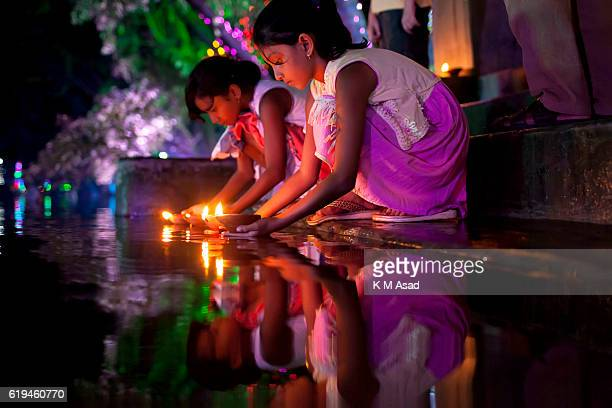 Bangladeshi young girls put oil lamps into a pond when they celebrate the Diwali festival or the 'festival of lights' at a temple in Dhaka Diwali is...