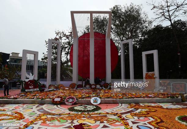 Bangladeshi youth decorate the Bangladesh Central Language Martyrs' Memorial monument with flowers in homage to the martyrs of the 1952 Bengali...