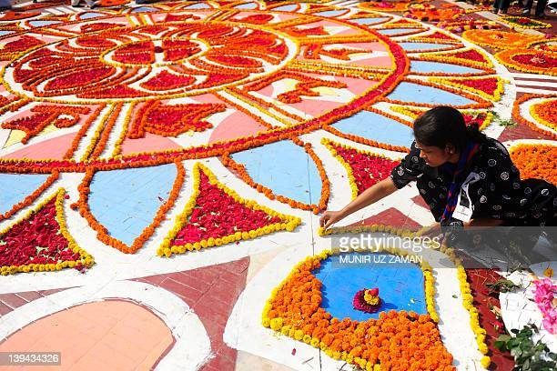 A Bangladeshi youth decorates the Central Language Martyrs' Memorial monument at Dhaka University in Dhaka on February 21 to pay homage to the...