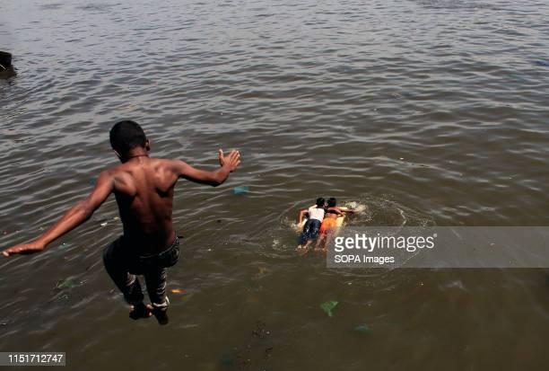 Bangladeshi youth dives into Buriganga River during a hot summer day in Dhaka