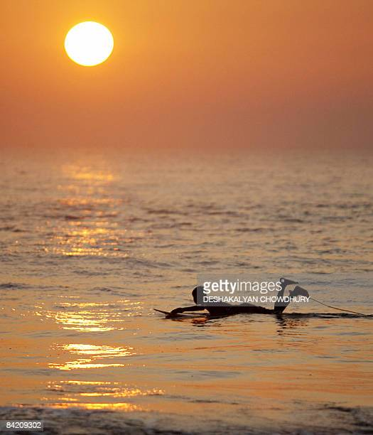 A Bangladeshi youth paddles his surfboard as the sun sets in Cox's Bazar Chittagong on January 7 2009 Cox's Bazar is known for its wide sandy beaches...