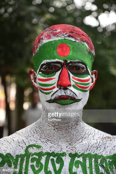 A Bangladeshi youth protest against violence on Rohingya people of Myanmar painted protest slogan his body and with national flag in front of...