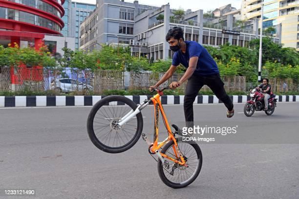 Bangladeshi youth shows off his balancing skills as he performs stunts on a bicycle at Agargaon road in Dhaka city.