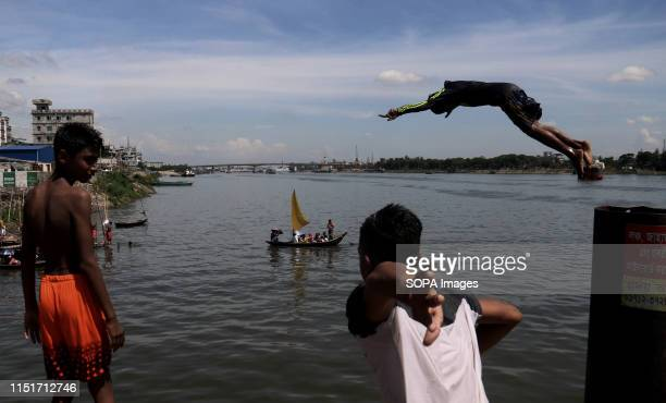 Bangladeshi youths dive into Buriganga River during a hot summer day in Dhaka
